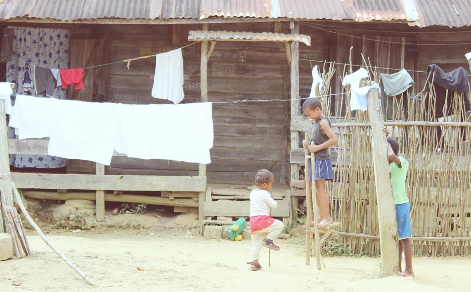 洗濯物が干された家の前で竹馬に乗るマダガスカルの子供たち